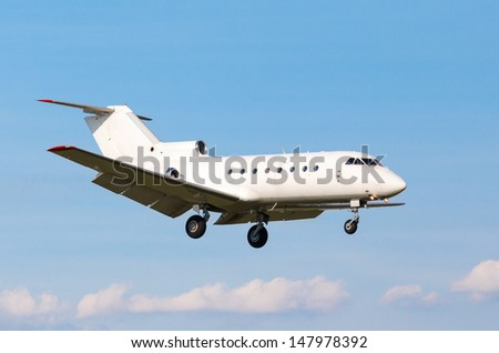 view from below on the white private jet with the gear against the blue sky