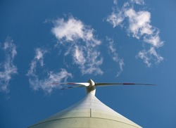 View from beneath the wind turbine directly to the rotor blade. Some clouds framing the rotor blades.