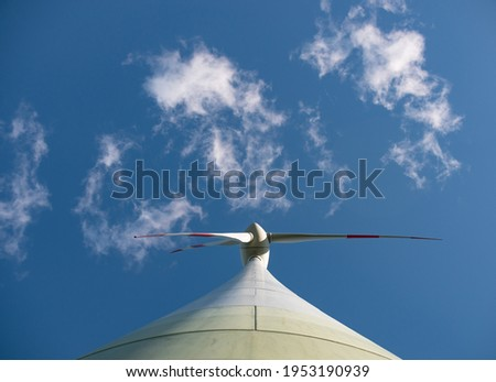 View from beneath the wind turbine directly to the rotor blade. Some clouds framing the rotor blades. Foto d'archivio ©