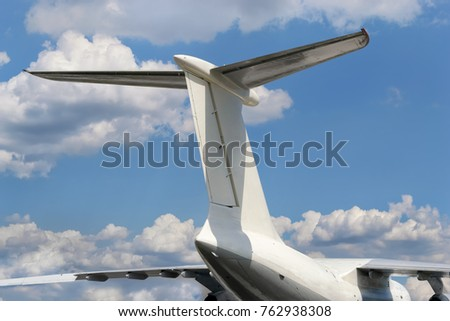 View from bottom on airplane tail with horizontal stabilizer against of a cloudy sky background