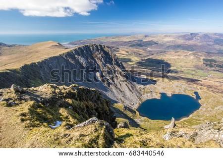 View from Cadair Idris (Penygader or Cader Idris) mountain: lake Llyn y Gader, and Irish sea at the horizon. Wales, at the southern end of the Snowdonia National Park near the town of Dolgellau.