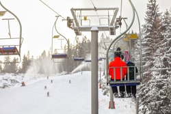 View from chairlift over ski piste, skier in bright red jacket seating in front, more blurred people skiing below, active snowguns background.