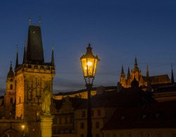 View from Charles Bridge on Mala Strana bridge tower with glowing street lamp nad Prague Castle at night, dark blue sky