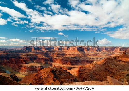 View from Dead Horse Point of the Colorado River with blue sky and clouds