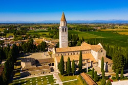 View from drone of medieval Basilica di Santa Maria Assunta, principal church in small Italian town of Aquileia on sunny autumn day