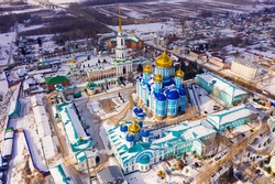 View from drone of Zadonsk Monastery of Nativity of Virgin with golden domes of St. Vladimir Cathedral and St. Nicholas of Myra Church belfry on winter day, Russia