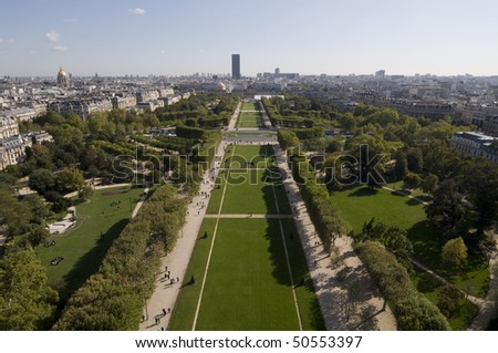 View from Eiffel Tower over Parc du Champs de Mars. Famous landmarks include les invalides to the left and tour montparnasse in the distance and ecole militaire at the end of the boulevard.