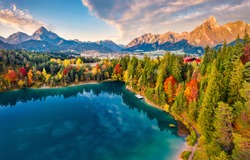 View from flying drone. Majestic morning scene of Urisee lake. Fabulous autumn view of Reutte town, Austria, Europe. Fantastic sunrise in Austrian Alps. Traveling concept background.