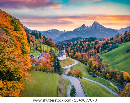 View from flying drone Maria Gern church with Hochkalter peak on background. Fantastic autumn sunrise in of Bavaria Alps. Fantastic evening landscape of Germany countryside.
