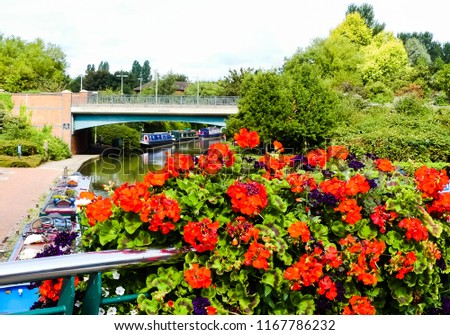 View from footbridge over Oxford Canal, Banbury, with colourful annuals in foreground, looking towards an empty road bridge. with moored canal boats along the towpath.  #1167786232