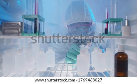 View from fridge of lab technician in protective overall and mask taking bottle with chemicals from refrigerator. Doctor taking medicine from fridge in hospital