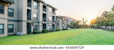 View from grassy backyard of a typical apartment complex building in suburban area at Humble, Texas, US. Sunset with warm light. Panorama style. #656604724