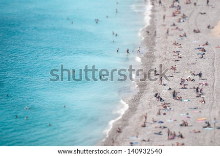 View from height of ocean beach with people bathing in clear blue water and tanning on soft sand. Summer holidays and vacations in hot countries and on resorts. Recreation and tourism.