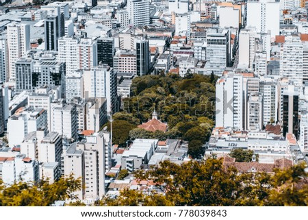 View from high point of modern urban cityscape on very bright summer day: multiple multistorey residential and office buildings, park with church in center, streets with people; Juiz de Fora, Brazil