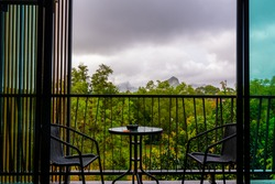 View from hotel room window with balcony to tropical forest during the storm with rain. Big shadow clouds and rainy weather. Two chairs on the side with simple table.