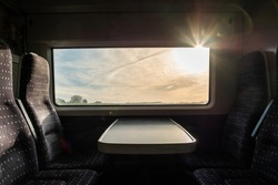 View from inside a english high speed train, travel to destination with noone on board. Trains empty during uk pandemic lockdown. View of the harsh morning sun outside the window