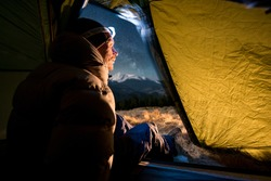 View from inside a tent on the male hiker have a rest in his camping at night. Man with a headlamp sitting in the tent near campfire