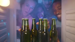 View from inside steamy fridge of young happy diverse people opening refrigerator taking bottles with cool beer celebrating event at house party together