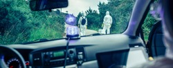 View from inside the car of people in bacteriological protection suits doing research on an empty road