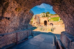 View from inside the stone arch of ruine of Greco-Roman theater, Sicily, Itale, Europe. Bright morning cityscape of Taormina town and Etna volcano on background. Traveling concept background.