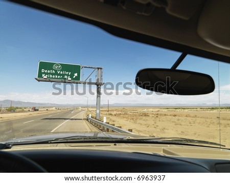 View from inside vehicle on desert highway with sign pointing towards Death Valley.