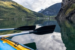 View from kayak vessel with two paddles above water surface. Norway Aurlandsfjord fjord travel, kayaking tour. Nature, mountains, blue landscape, cloudy epic view.