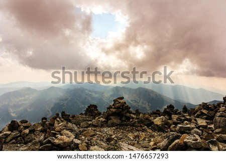 View from mountain peak on rocks, sunrays, cloud and other mountai peaks in the distance.