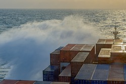 View from navigation bridge to a large wave crashing into bow of container ship in the stormy sea.