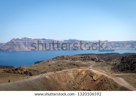 View from Nea kameni in Greece over the island of Oia and Thira. Tourists and cruiseship.