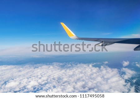 View from porthole with silver wing, blue sky, white clouds and horizon; Flight above the clouds; Sunny cloudscape #1117495058