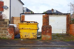 View from road side of industrial rubbish skip near footpath for background use. Space to add text on surrounding blurry area near the bin, footpath, road surface, houses. Renovate, skip hire concept.
