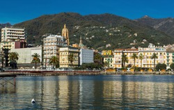 View from sea of seafront of Italian town of Rapallo with belltower and dome of basilica