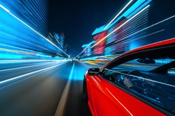 View from Side of a Red Muscle Car moving in a night city, Blured road with lights with car on high speed. Concept rapid rhythm of a modern city.