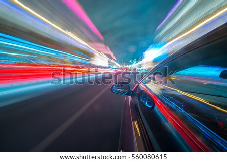 View from Side of Car moving in a night city, Blured road with lights with car on high speed. Concept rapid rhythm of a modern city. #560080615