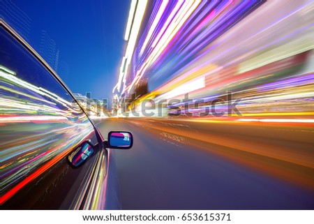 View from Side of Car moving in a night city, Blured road with lights with car on high speed. Concept rapid rhythm of a modern city. #653615371