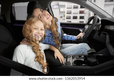 View from side of pretty girl sitting in new car with mother in auto salon. Cheerful family hugging, looking at camera and smiling. Happy clients choosing and testing automobiles in showroom. #1362053954