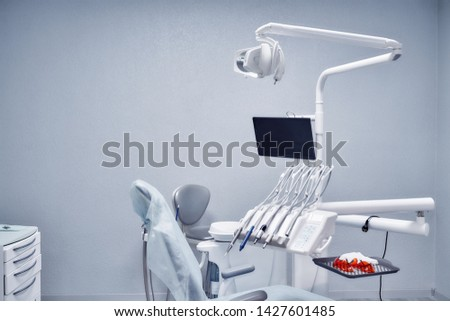 View from side of professional medical equipment and tools for dental procedures. White devices, modern devices and comfortable seat in dentist office in clinic. Concept of stomatology. #1427601485
