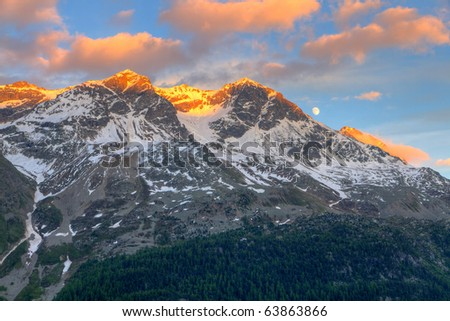 view from St. Moritz in Switzerland: high snow and ice capped alpine mountain range with red illuminated peaks at sunset and the moon out
