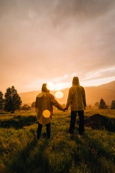 View from the back. Photo with highlights. Couple of young hikers standing in the rain holding hands in the mountains at sunset and looking at the unreal landscape.