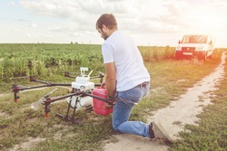 View from the back process of preparing agro drones for irrigation. A man agronomist pours liquid into a Octocopter .