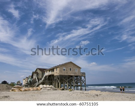 View from the beach showing a beautiful cloudscape and the sand bags around a row of condemned homes in Nags Head North Carolina in the Outer Banks.