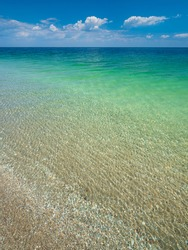 view from the beach to to emerald calm waters of sea under blue sky with copy space