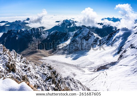 View from the bird\'s-eye over the mountains and clouds from Uku pass.Glacier below. Picture was taken during trekking hike in the beautiful Caucasus mountains, Bezengi region,Kabardino-Balkaria,Russia