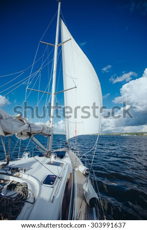 View from the board of a sailing yacht on the waters, sailing ships and the forest growing along the coast, as well as people\'s homes. sailing yacht floating in the wind on a beautiful sunny