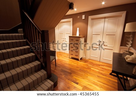 View from the bottom of a staircase of a wooden floored hallway in a luxury home.