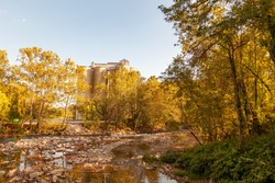View from the bridge over Patapsco river at Ellicott City,MD in autumn. Image features the river with a rocky bed, trees with autumn colors, fallen leaves and a historic flour mill behind trees.