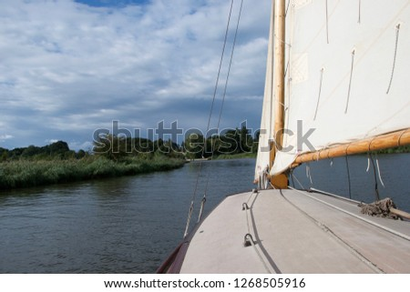 View from the cabin top of a traditional sailing boat on the Norfolk Broads, England, on a sunny day in summer