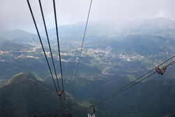 View from the cable car cabin to the mountain valley and the city under low clouds, top view