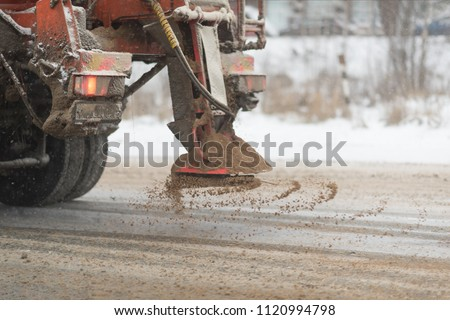 View from the car behind orange highway maintenance truck spreading de-icing salt and sand, crystals dropping on the ice covered asphalt road. - Shutterstock ID 1120994798