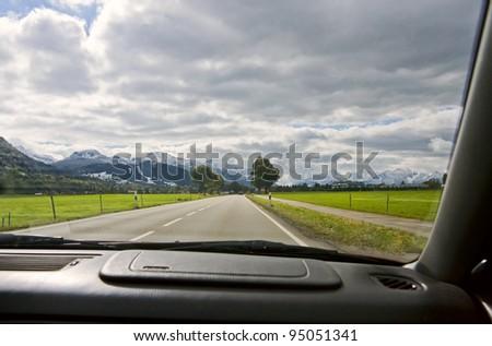 View from the car window to the road and mountain landscape. Bavarian Alps, Germany - stock photo
